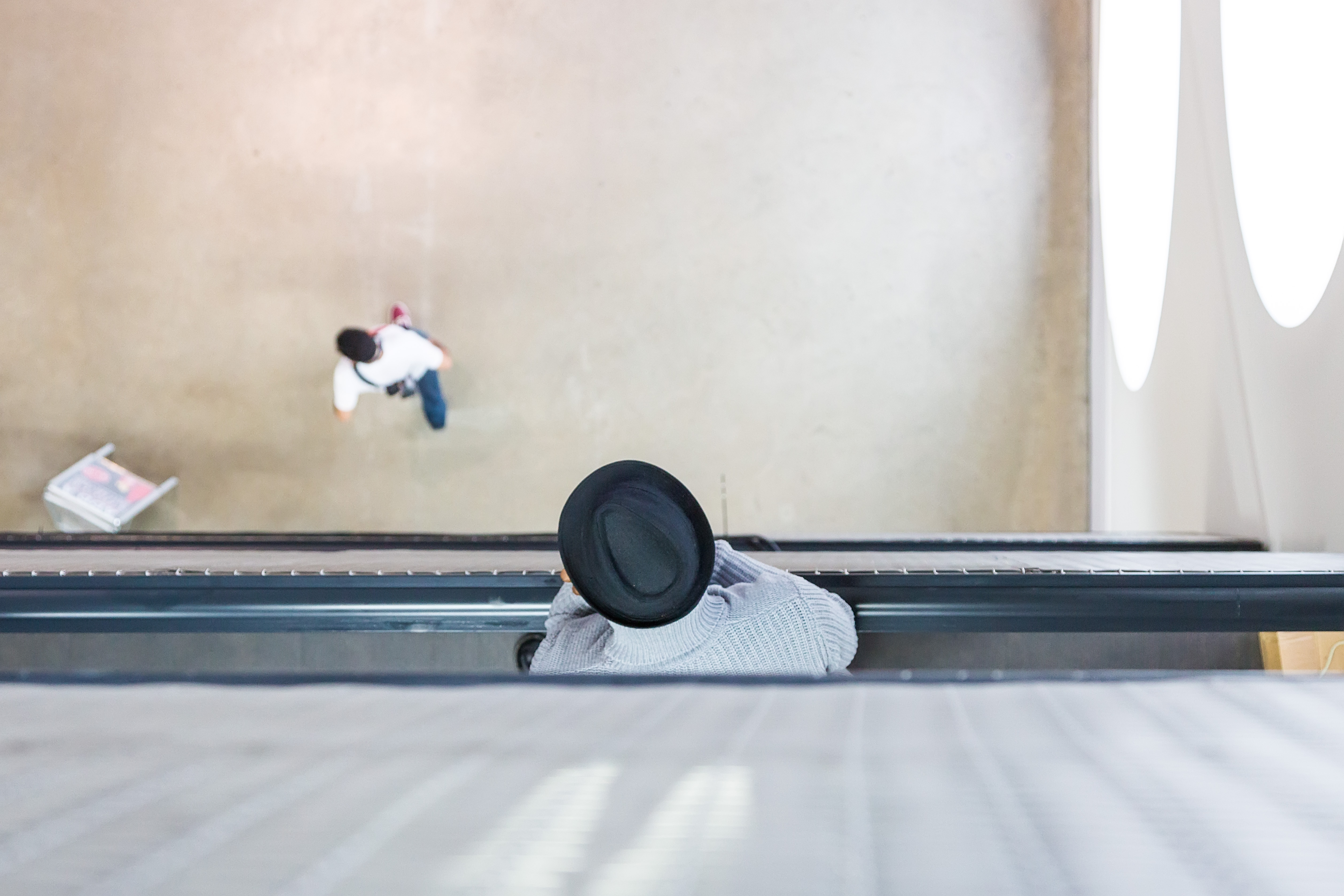 A man with a hat looking down from a balcony